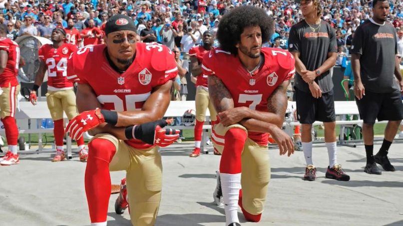 Colin Kaepernick kneeling, photo via The AP