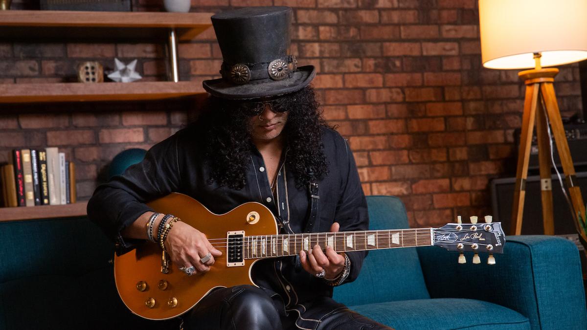Slash Goldtop seated Slash Unveils Gibson Victoria Les Paul Standard Goldtop Electric Guitar